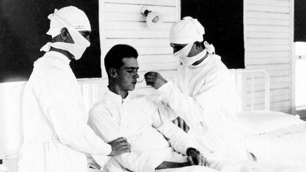 Os médicos tratam um paciente com gripe em Nova Orleans, nos Estados Unidos, em 1918