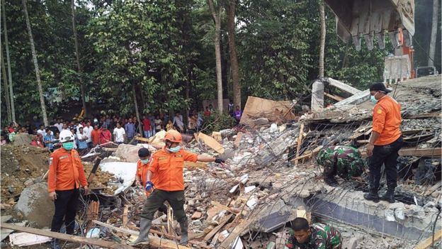 Indonesian search and rescue personnel stood next to a pile of rubble from a collapsed building in Aceh province on 7 December 2016.