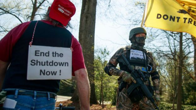 A protester open carries an AR style black military type rifle during a demonstration against Indiana's stay home orders