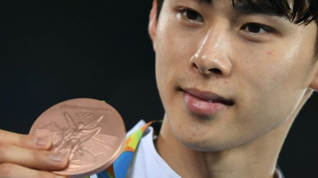 South Korea's Kim Sohui poses with his bronze medal after the men's taekwondo