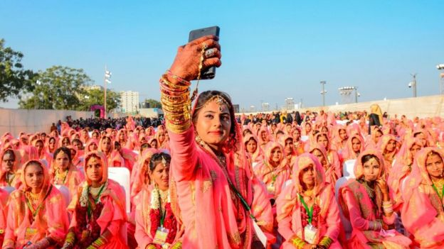 A Muslim bride takes a selfie with her mobile phone as she participates in an 'All Religion Mass Wedding' ceremony at Sabarmati Riverfront in Ahmedabad on February 8, 2020