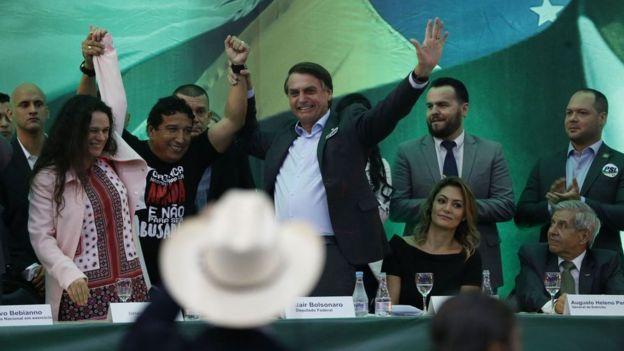 Em pé, Paschoal e Bolsonaro aparecem sorrindo durante evento que oficializou o nome dele na eleição de 2018, da qual saiu vencedor, em meio a outros correligionários