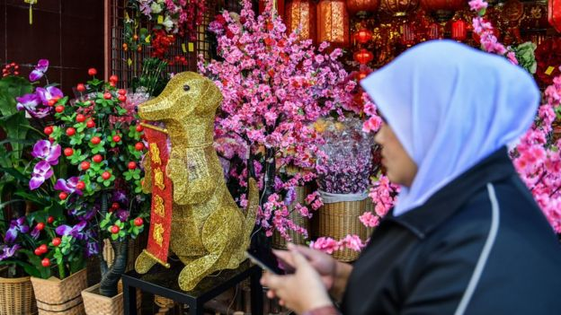 A Muslim woman walks past a golden canine statue ahead of the Lunar New Year celebrations in Kuala Lumpur's Chinatown