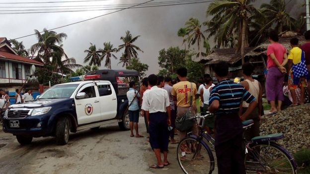 This picture taken on 27 August 2017 shows a police vehicle and people next to houses burnt in Maungdaw township in Rakhine State in Myanmar