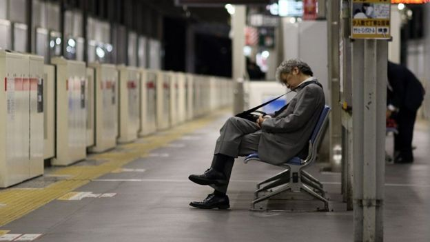 Businessman asleep at a train station in Japan