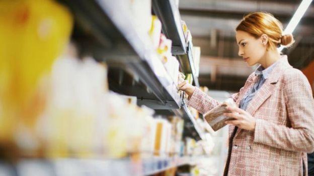 Mulher escolhendo produtos em prateleira