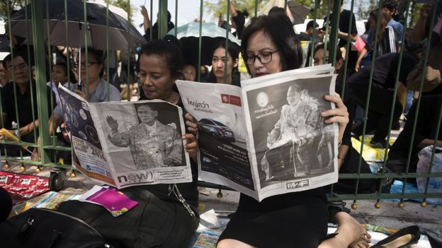 Thai women read newspapers covering the death of King Bhumibol Adulyadej