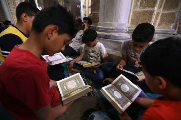أطفال مسلمون في غزة يقرأون آيات قرآنية في أول أيام رمضان في جامع العمري في غزة. 06 مايو/أيار 2019