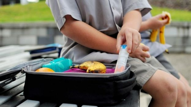Young boy with a packed lunch takes out his anaphylaxis auto injector