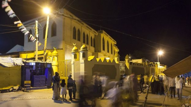 People walk in front of the Jimma Mosque, the largest mosque in Harar, especially reserved for Friday prayers, on August 3, 2014