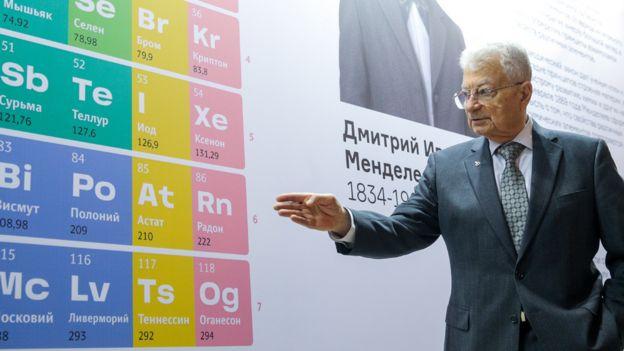 Yuri Oganessian frente a una gran tabla periódica