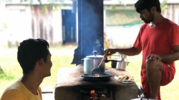 Joelmir e outro homem em cozinha externa com fogão à lenha