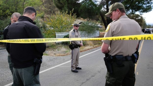 Officers stand near one of the crime scenes of the shooting