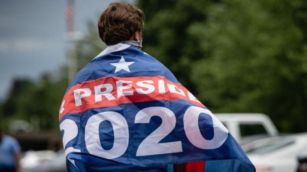 JOven que apoya a Biden con una bandera en la espalda