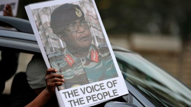 A person holds a sign featuring Commander of the Zimbabwe Defence Forces, Constantino Chiwenga as people take part in a demonstration demanding the resignation of Zimbabwe's president on November 18, 2017 in Harare.