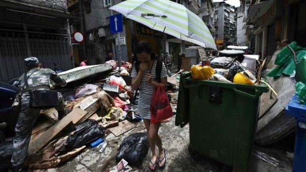 澳门内港十月初五街一名女士掩鼻走过解放军驻军正在清理的垃圾堆(25/8/2017)