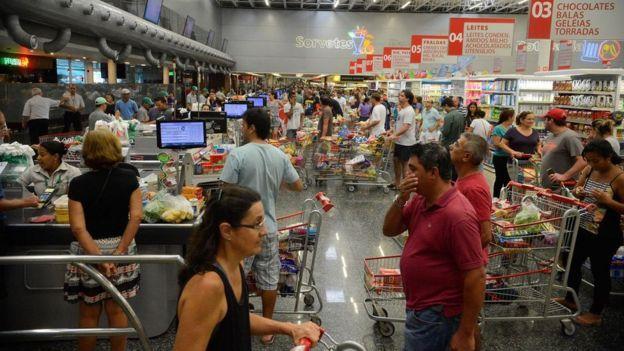 Imagem mostra interior de loja de supermercado, com consumidores, carrinhos de compra e trabalhadores do estabelecimento
