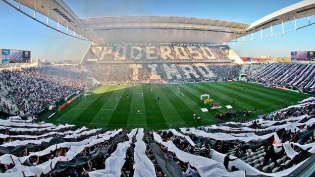 Arena Corinthians lotada de torcedores do time, cuja torcida forma a palavra 'poderoso timão'
