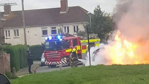 Car on fire with fire engine and armed police in attendance