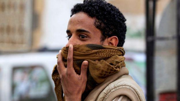 يمني يغطي فمه وأنفه بالغترة أو الشال اليمني
