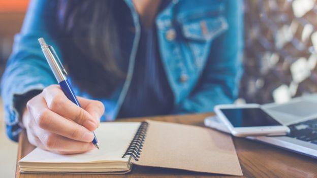Mulher sentada escrevendo em caderno ao lado de celular e laptop na mesa
