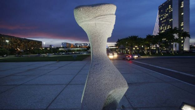 A estátua que representa a Justiça, em frente ao prédio do STF, durante anoitecer em Brasília