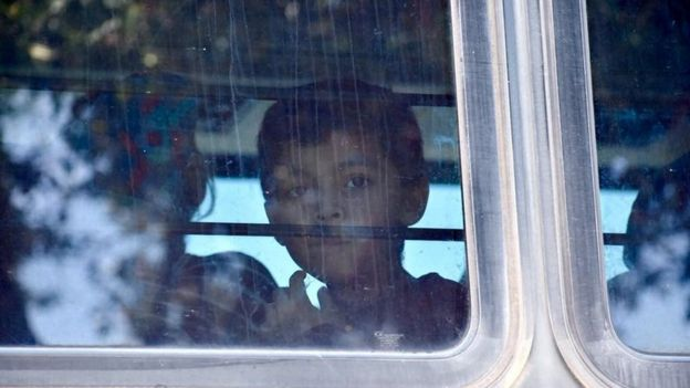 A child looks through the window of a bus carrying migrants near McAllen Detention Facility, McAllen, Texas