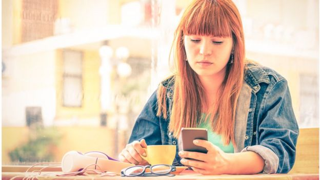Mulher olha seu celular