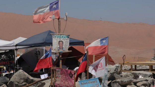 Mensajes de ánimo y banderas de Chile fuera de la mina.