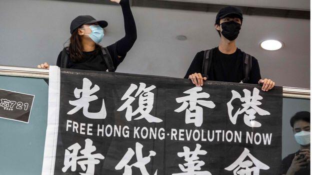 有示威者英语学习网举起标语表达诉求。