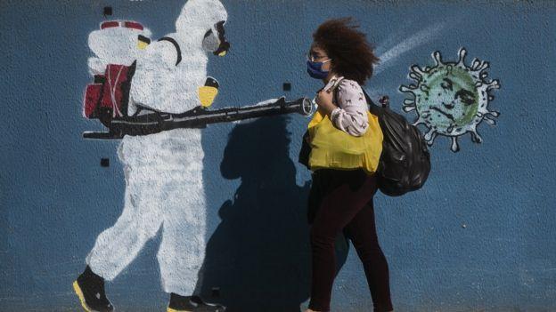 Mulher passa por mural de rua no Brasil