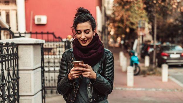 Joven caminando y mirando el celular