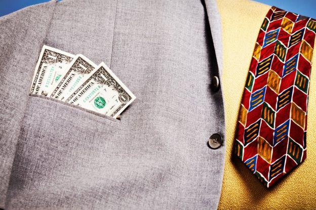 Billetes de dólar sobresalen del bolsillo de una chaqueta dejada sobre un sofá, junto a una corbata.