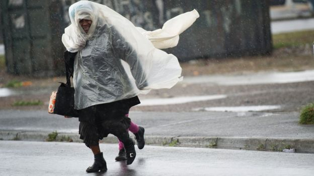 A woman and a child run across the road in makeshift raincoats in an informal settlement in Langa during one of the most intense storms that has hit the Western Cape Province in more than a decade