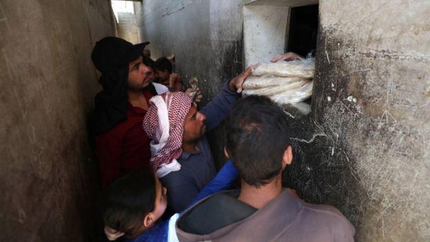 سوريون في إدلب يقفون أمام فرن للخبر