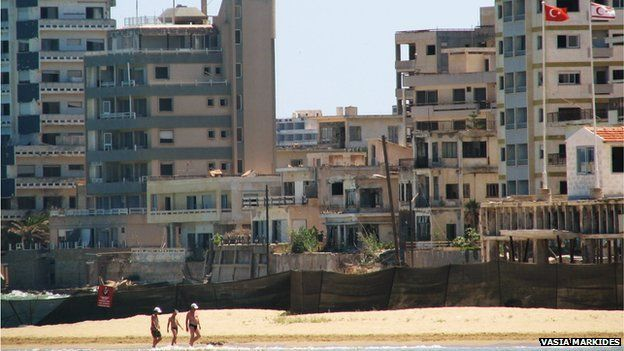 People walking on the beach with Varosha in the background