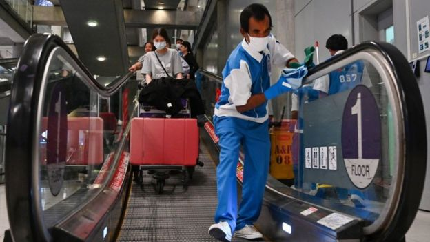 A worker wearing a protective facemask cleans the handrails at the passengers' arrival area of Suvarnabhumi Airport in Bangkok