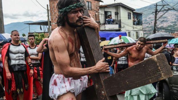 Hombre que interpreta a Jesús carga la cruz.