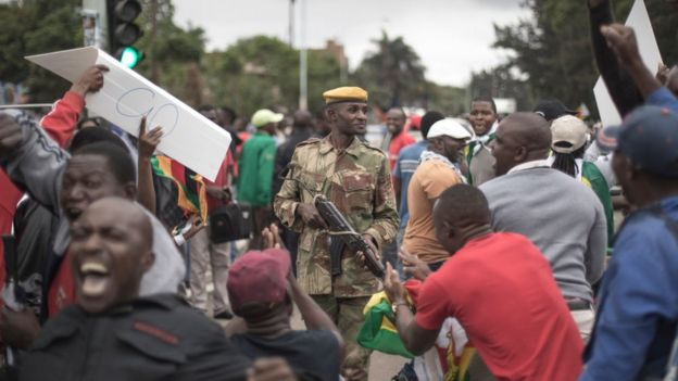 Protesters demanding President Robert Mugabe stand down, look up and cheer as an army helicopter flies over the crowd, as they gather in front of an army cordon on the road leading to State House in Harare, Zimbabwe Saturday, Nov. 18, 2017.