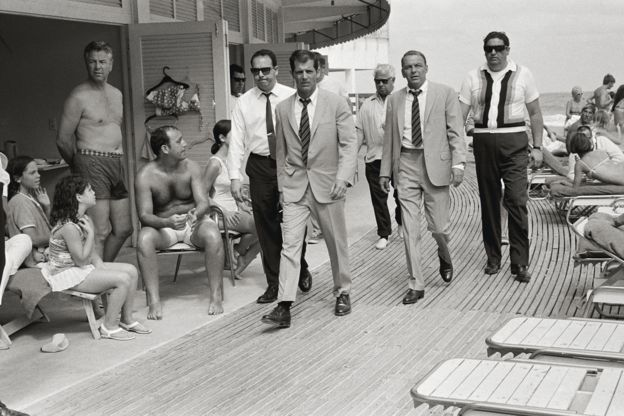 Frank Sinatra with his minders and his stand in (who is wearing an identical outfit to him), arriving at Miami Beach while filming The Lady in Cement