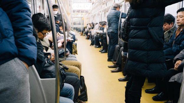 ركاب يتجهون إلى أعمالهم في قطار في اليابان وبعضهم يغلبه النعاس