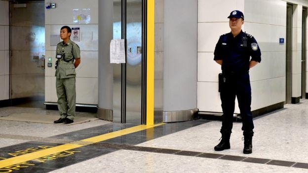香港海关关员与中国大陆警员在香港西九龙高铁车站内于口岸区界线两侧站岗(18/9/2018)