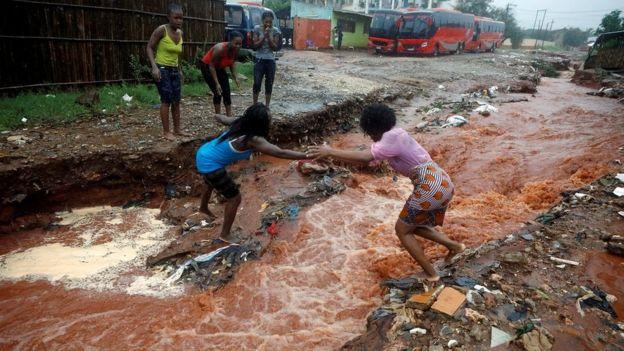 Pessoas em meio a enchente em Moçambique