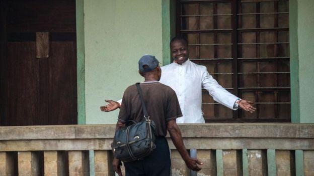 Le père Lucien Ambunga, un prêtre qui a survécu au virus Ebola, accueille un fidèle à l'église Saint Joseph d'Itipo, en RDC.