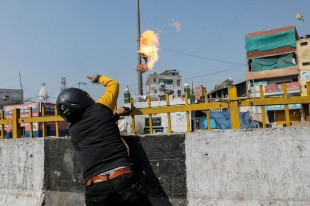 A man supporting a new citizenship law throws a petrol bomb at a Muslim shrine during a clash with those opposing the law in New Delhi India, February 24, 2020