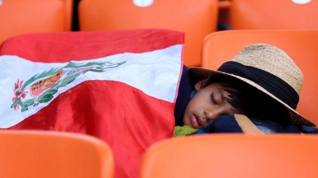 Un niño duerme en un estadio.