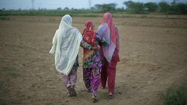 Women walking away from camera in Indian field