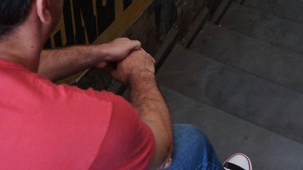 Jorge sentado em escadaria