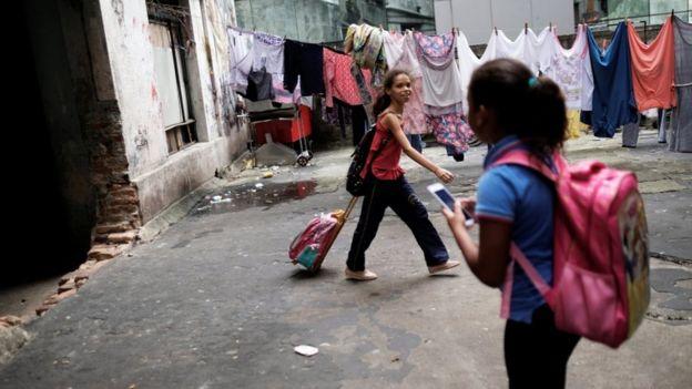 crianças na ocupação Prestes Maia, antiga fábriga textil, com mochilas escolares