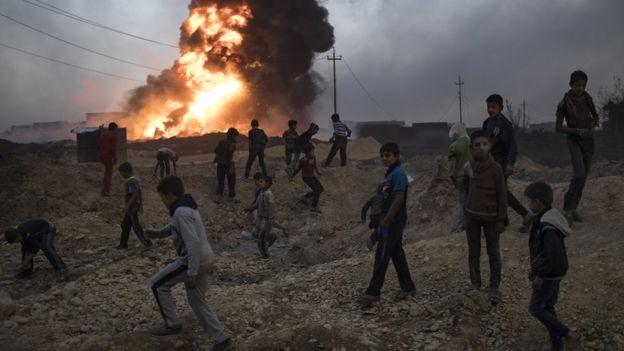 Crianças nos escombros e fogo ao fundo